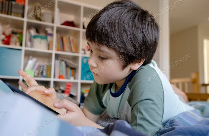 Kid self isolation using tablet for his homework, child lying in bed using digital tablet