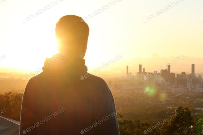 Inspirational moment - a young man looks over the Brisbane city skyline at sunrise