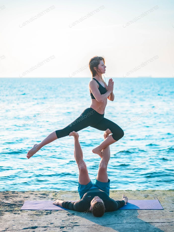 Young beautiful couple practicing acro yoga on the sea beach near water