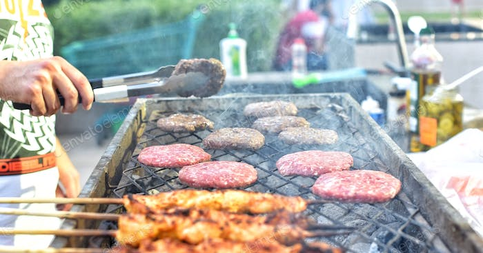 Burgers and chicken cooking on the grill with unrecognizable person