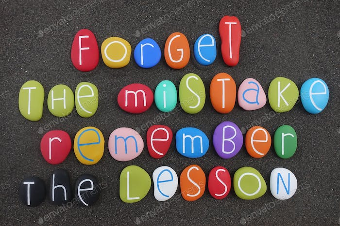 Forget the mistake, remember the lesson, creative and motivational phrase on colored stones