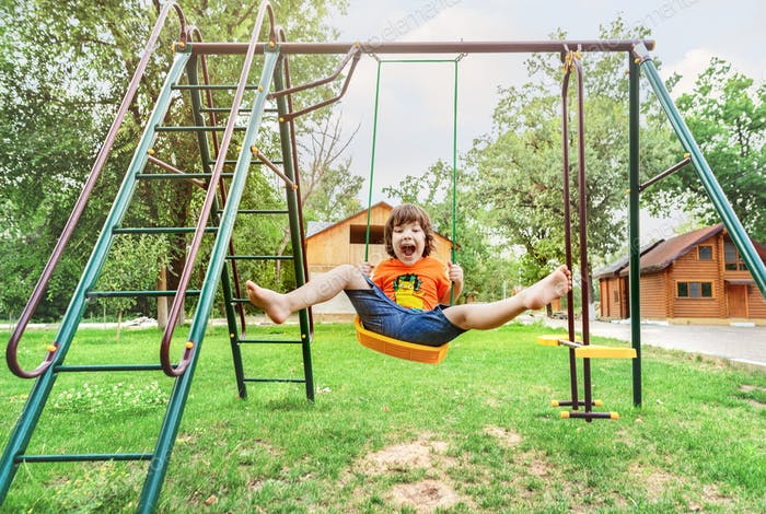 A boy rides on a swing. The boy is in a good and happy mood.