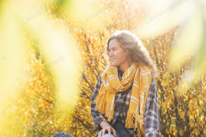 Young woman with curly hair traveller looks at magic view of autumn nature