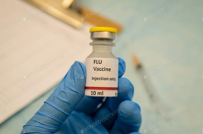 Grippekontrolle durch Grippe-Impfstoff in der Hand halten