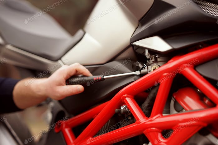 Technician hands of motorbike mechanic repairing the vehicle with the wrench
