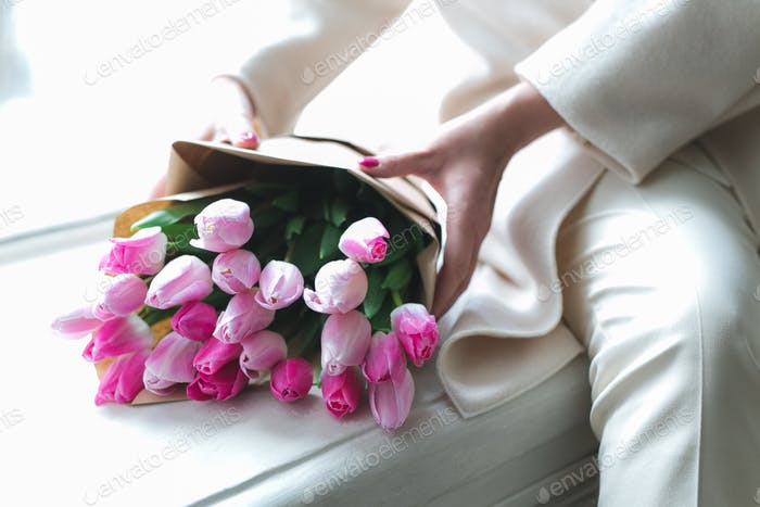 beautiful spring flowers tulips lie on the windowsill, female hands