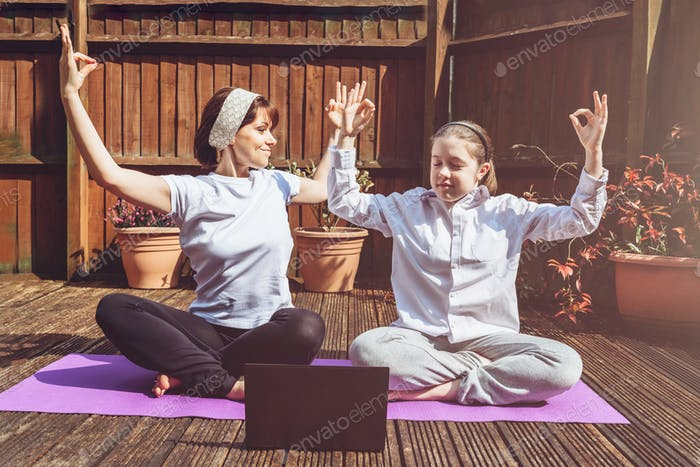 Happy Mother and Daughter are doing online yoga with laptop during self isolation at their back