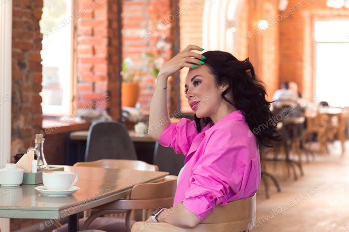 Woman brunette pink shirt sitting in cafe with cup of coffees