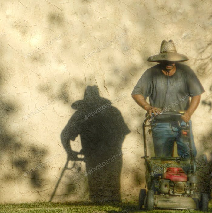 The gardener is mowing the lawn and casting a shadow on the wall.