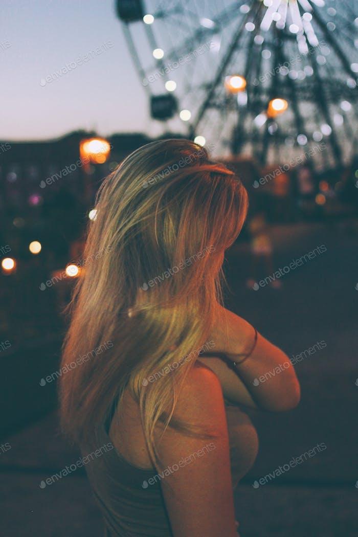 Young beautiful blonde girl walking in the Park, night lights Ferris wheel