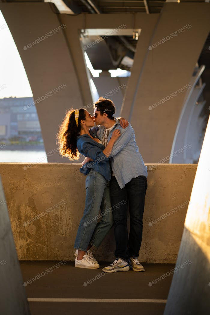 Romantic couple of young male and female embracing and kissing at sunset standing under urban bridge