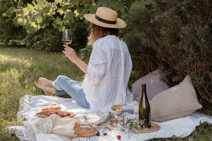 Woman having picnic by her self alone with wine glass. Aesthetic picnic outdoors. Woman from behind