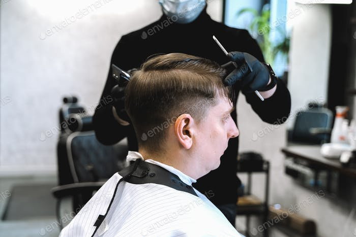 Visit to barbershop.Man makes fashionable haircut,hairdress.Shaved temples,sides.Barber hair clipper