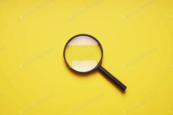 loupe or magnifying glass on yellow background with copy space