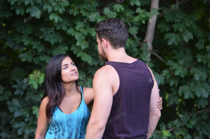 Latino couple have a discussion in the park.