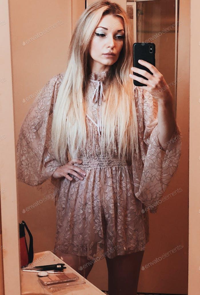 Beautiful blonde girl with long hair taking selfie