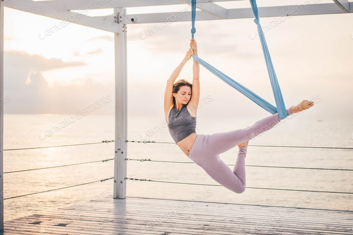 Woman doing yoga in a hammock.