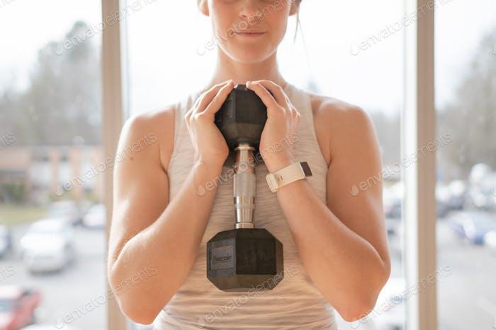 Woman holding free weight in goblet position in a gym