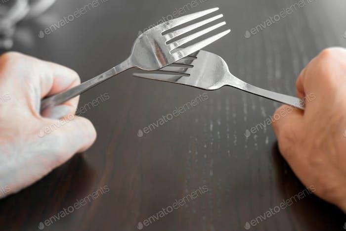 Punto de vista manos sosteniendo dos tenedores mientras que en la mesa de comedor.