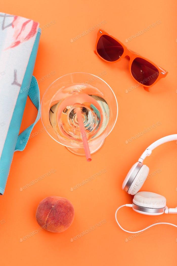Sunglasses, glass with drink, headphones, peach, blanket on orange background. Minimal summer style
