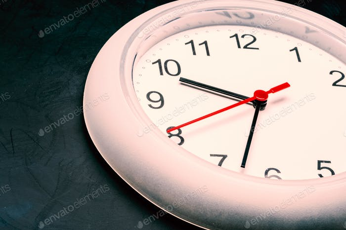 Time management, close up of an analog clock on dark background