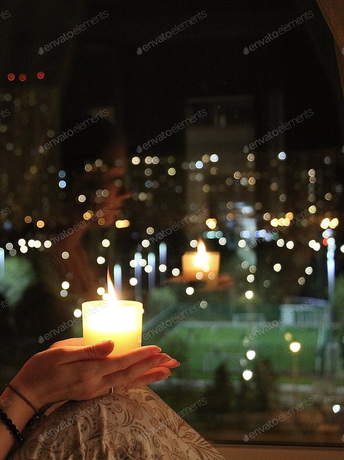 girl with a candle on the background of the window. reflection and magic divination