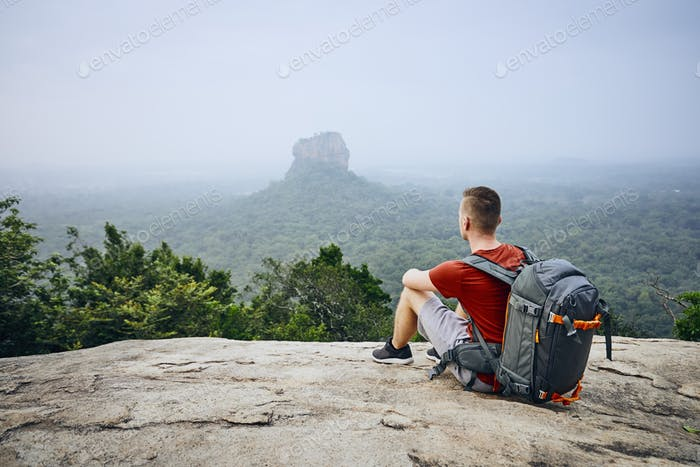Young man with backpack against Sigiriya Rock (UNESCO World Heritage Site)