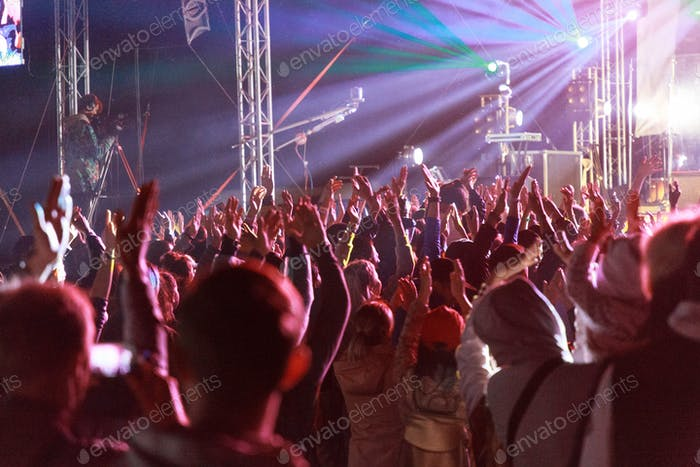 crowd of spectators clapping hands in the air in front of a stage at a concert