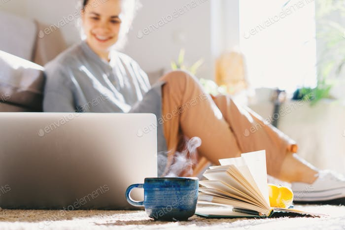 Woman working from home and using laptop at sunny room