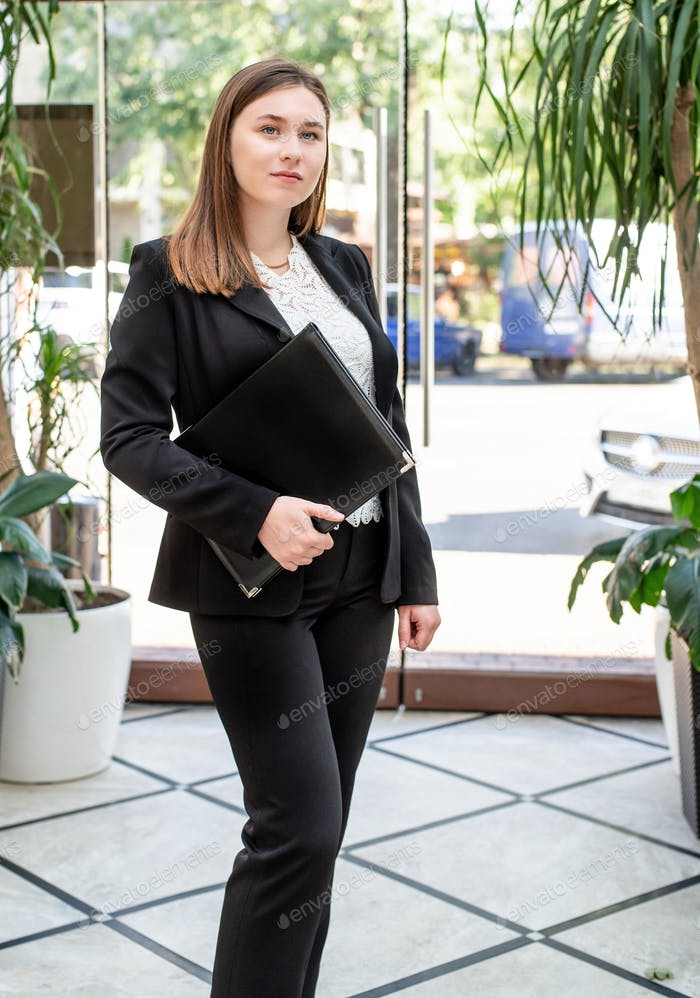 Young business woman in black suit standing in the office hall