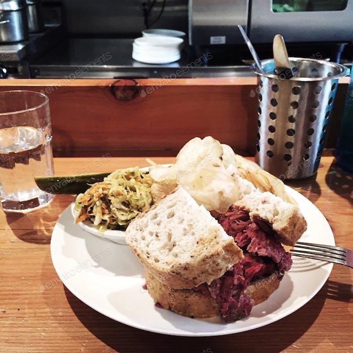 Cornedbeef-Sandwich mit Pommes, Krautsalat und Gurke