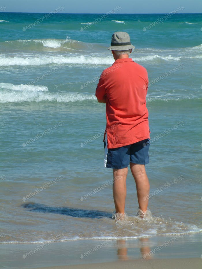 Senior man, standing at water's edge, looking out to sea.