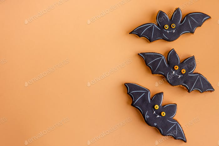 Holiday card for Halloween. Black bats, hand made gingerbread cookies isolated on orange background