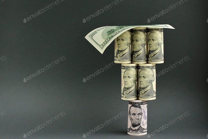 Enrolló billetes de dólar en forma de pirámide. Finanzas, tipo de cambio, moneda, concepto de economía.