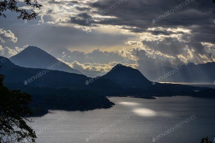 Guatemalan sun rays bursting through the clouds onto Lake Atitlan