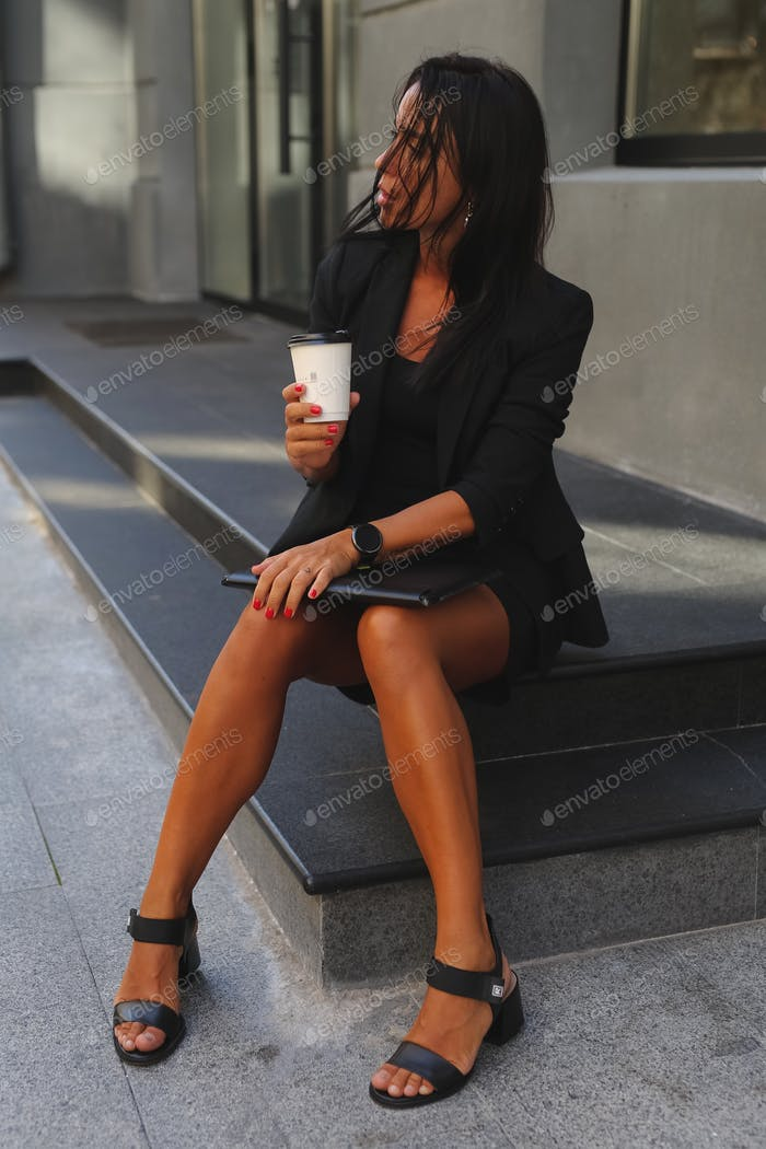 stylish girl,brunette,in a black suit,tanned,sitting in the city,working on a laptop,drinking coffee