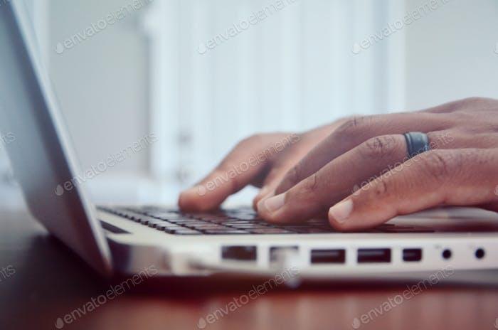 Man's hands on MacBook Pro keyboard