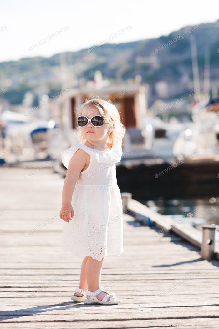 Stylish baby girl 2-3 year old wearing sun glasses outdoors. Looking at camera.
