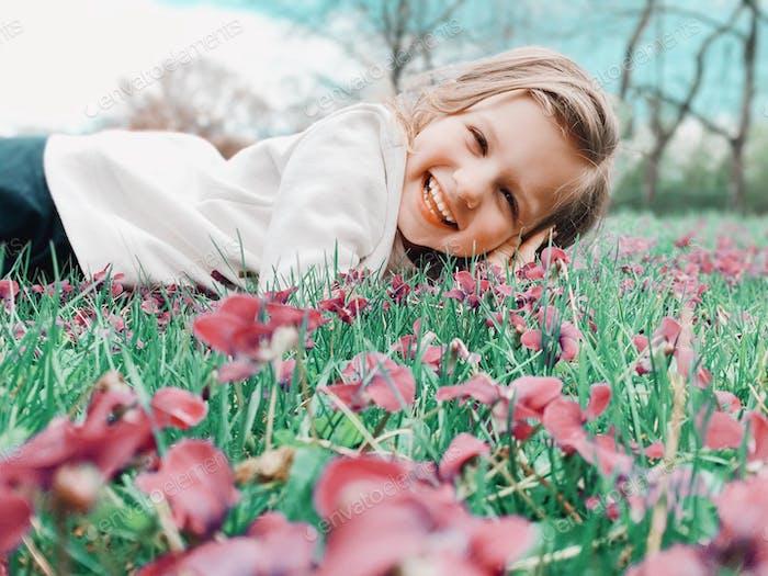 Kleines Mädchen in einem weißen Sweatshirt gekleidet und Jeans spielt draußen im Gras.