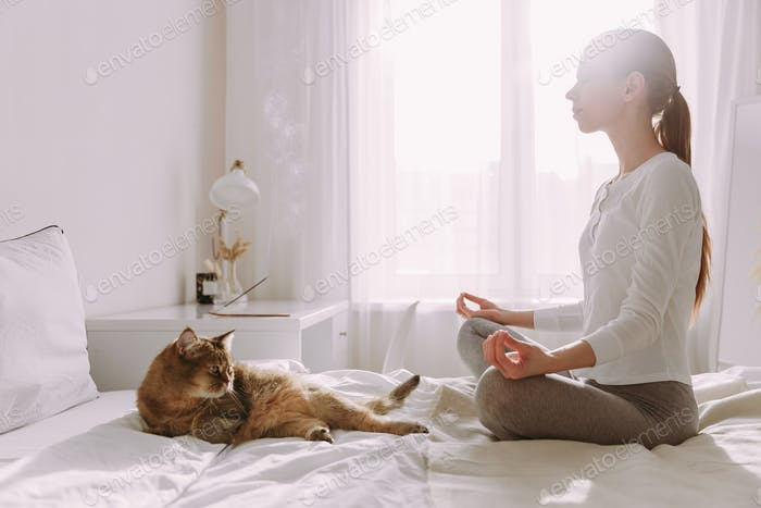 the girl sits on the bed in the bedroom and meditates with incense on a sunny morning, next to her c