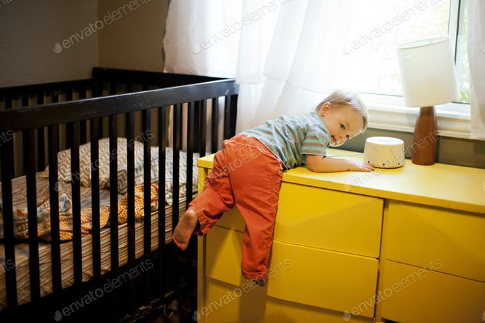 Toddler boy hanging off of s yellow dresser after crawling out of his crib
