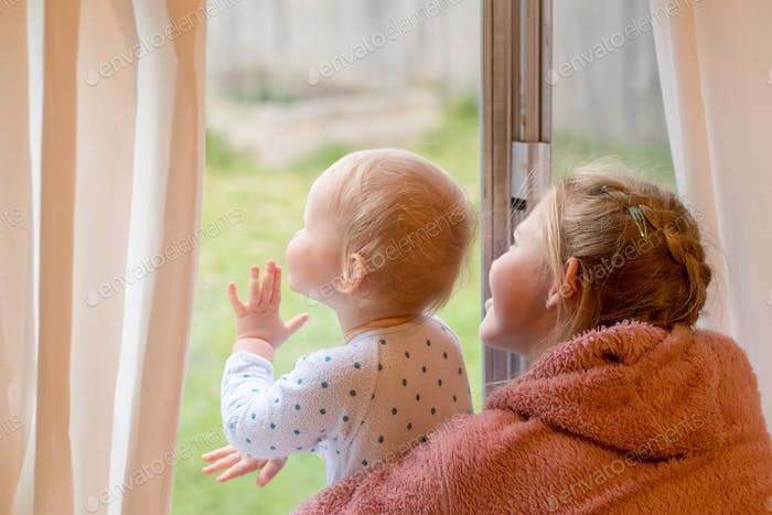 A blond girl holds her baby brother near the window. Self isolation coronavirus concept.