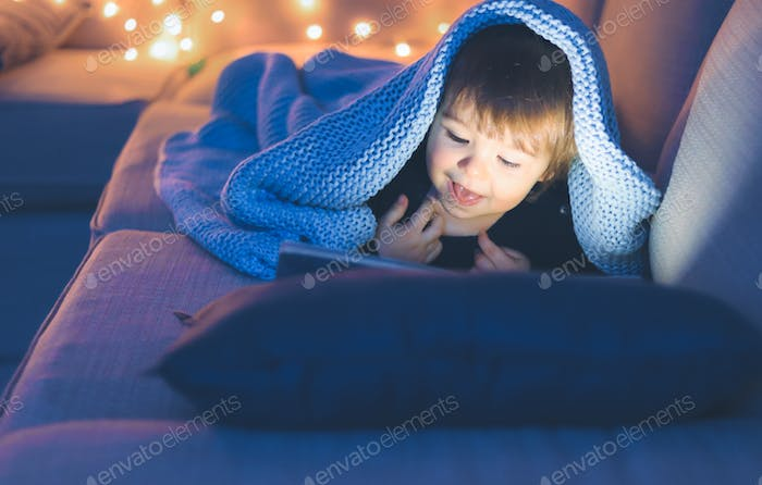 Child reading book under knitted blanket at winter night. Cozy vibes.