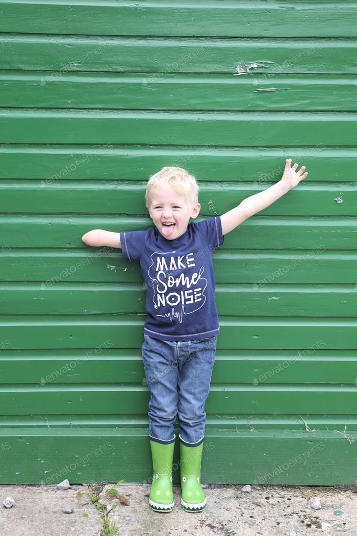 A child with a l imb difference standing in front of a green wall, arms outstretched and smiling. '