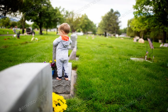 little toddler standing on a gravestone
