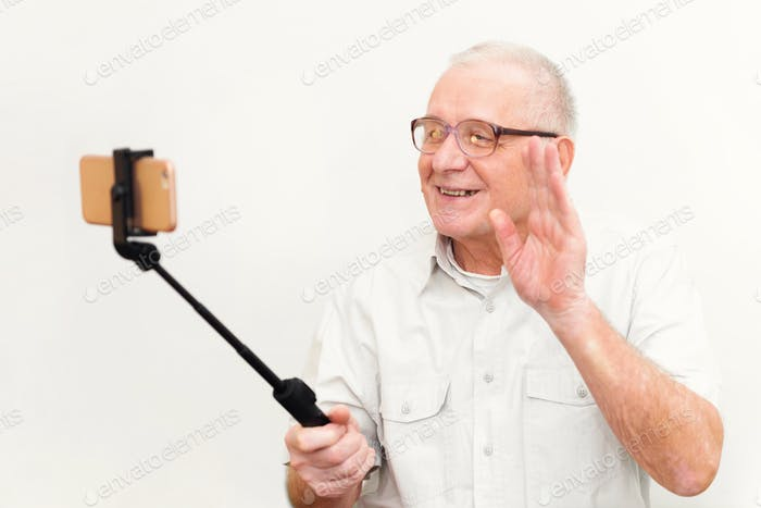 80s elderly man using selfie stick with phone