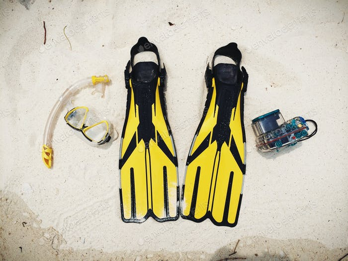 Snorkeling mask, underwater camera and fins on the white sands, just add water for your holiday