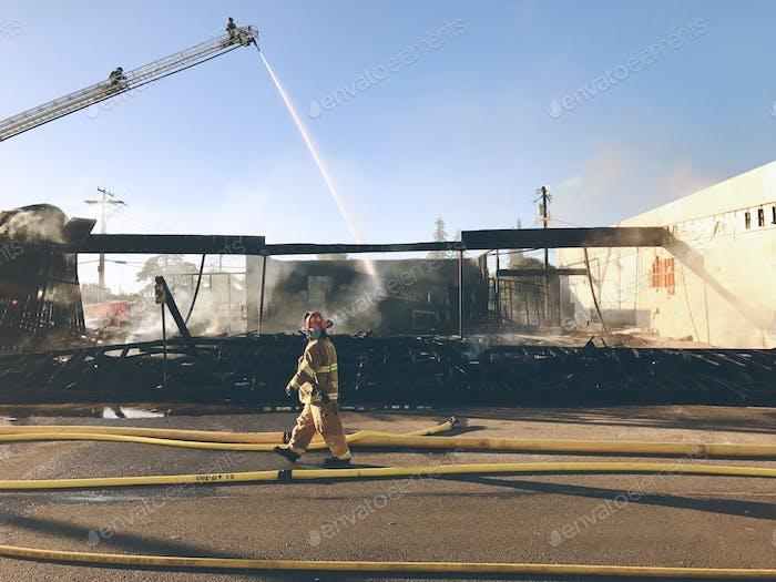 Fireman walking past burned out building.
