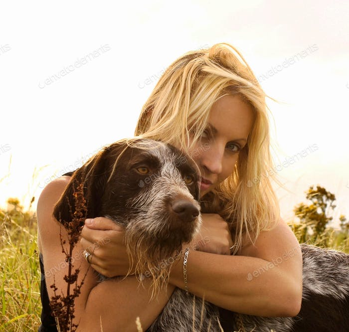 Blonde girl hugging her dog with both arms around his head ,true love...