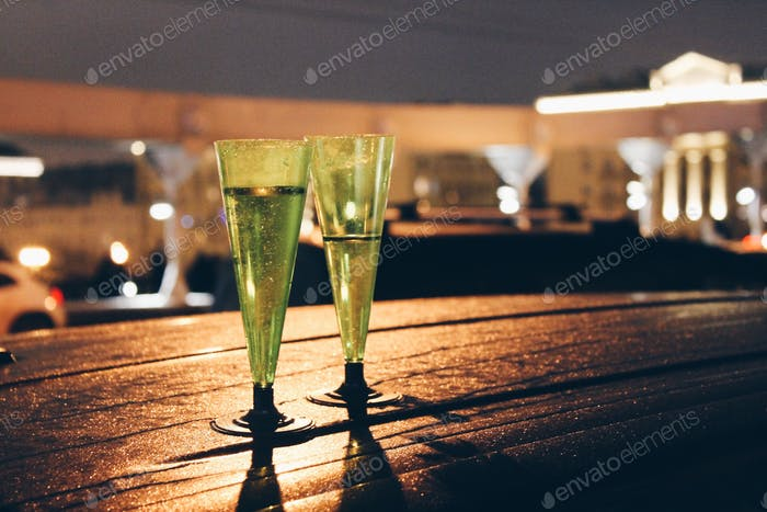 Two glasses with champagne on a roof of the car on New Year's Eve